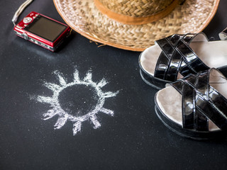 flat lay of summer lady accessories on black background with painted sun with chalk