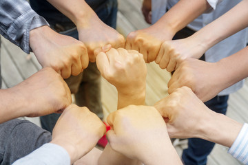 Image of young people putting their fists together by having a fist in the middle as symbol of unity and achievement, top view. Group of people fist bump assemble together. Concept teamwork