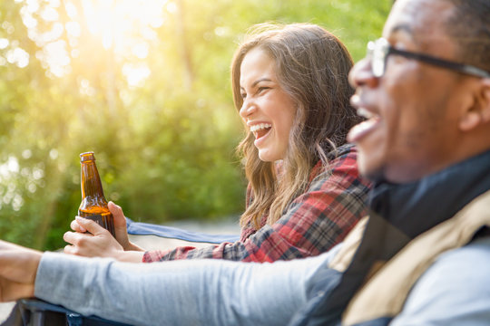 Young Adult Hispanic Girl with Bottle of Beer Enjoys Talking with Friends Outdoors