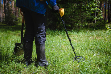 a man with a metal detector in the woods
