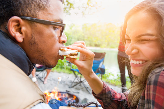 Young Adult Hispanic Girl Feeding African American Man A Smore at Campfire Outdoors