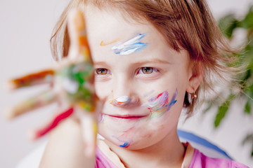 Art, creative and happiness concept. Colorful painted hands and face in a beautiful young girl.