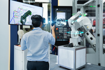 Engineer testing virtual reality glasses 3D scan with joystick programming automated robot industry in smart factory, Technology 4.0 concept
