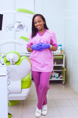 Young smiling black ethnic Afro-American female dentist assistant standing in dental office by chair. Handsome doctor in a pink uniform. modern equipment