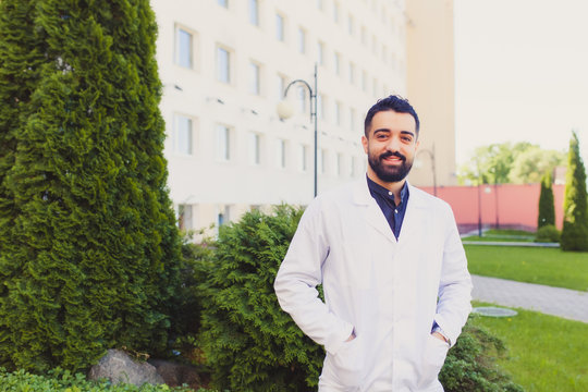 Portrait of friendly, smiling confident male doctor, medical professional with arms crossed. Health care reform. Arab student