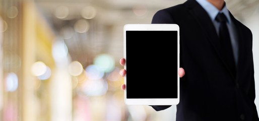 Businessman hand holding tablet with blank on screen display over blur background, business people and technology display montage, mock up, template, background