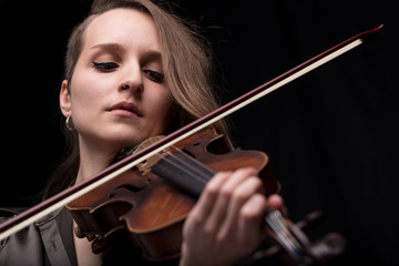 passionate violin musician playing on black background