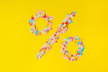 The Sign of percent, sign of a discount on a background from multi-colored confetti