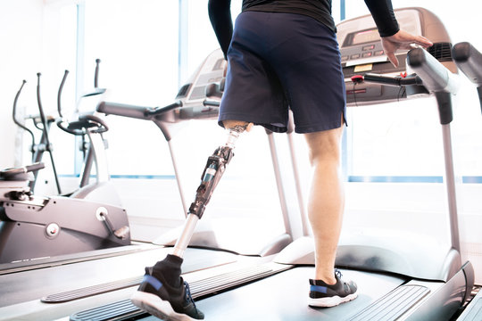 Low angle portrait of unrecognizable muscular man with prosthetic leg using walking on treadmill while working out  in modern sunlit gym