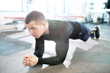 Full length  portrait of handsome muscular man with prosthetic leg doing push ups while working out in modern gym, copy space