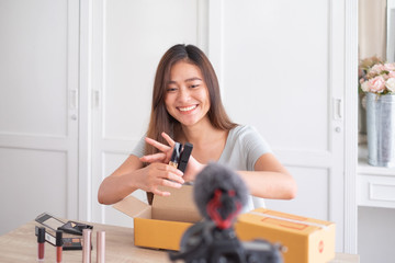 Asian woman blogger unpacking cosmetic, postal packet for reviewing, influencer ,social media