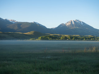 Fog in the Valley with Snow Capped Mountains in Background. Photographed in Paradise Valley Montana.