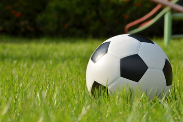 Football or soccer ball on green grass with morning sunlight,outdoor activities.