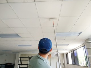 Close up of man at work painting a roof of new office, Copy space