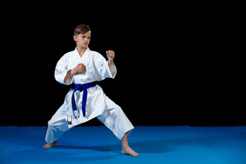 Pre-teen boy doing karate on a black background