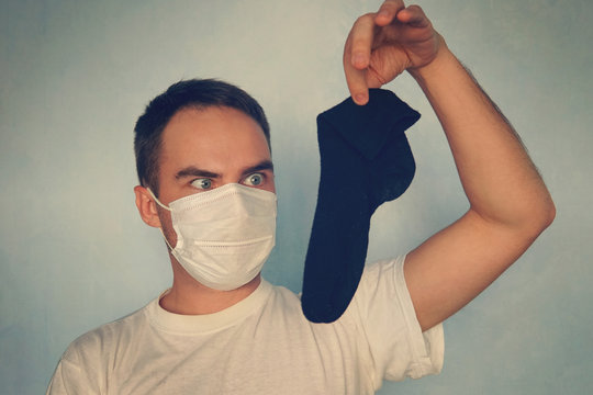 Man with gas mask is holding stinky sock - unpleasant smell concept.