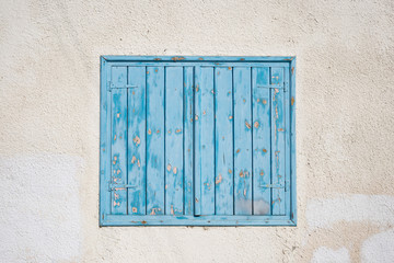 Cyprus, Larnaca. Blue wooden, peeled window, shutters on pink wall. Facade of building, closeup.