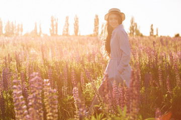 Beauty Romantic woman walking in field. Beautiful Teenage Model girl Dressed in Casual Short Dress and hat relaxing in warm color sunlight beams