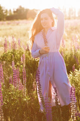 cheerful caucasian young woman on the field at sunset. Full lenght portrait toned warm color