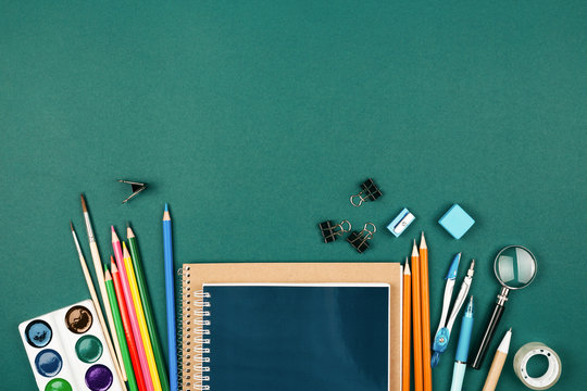 Pupil's desk with stationary on green background. Preparation to school.