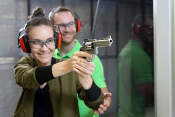 Strzelanie rekreacyjne na strzelnicy. Kobieta strzela z rewolweru pod okiem instruktora.