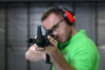 Strzelectwo. Mężczyzna strzela z karabinu na strzelnicy