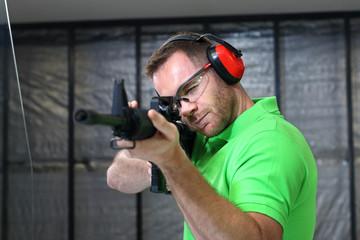 Strzelnica.  Mężczyzna strzela z karabinu na strzelnicy
