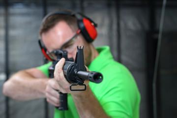 Mężczyzna strzela z karabinu na strzelnicy