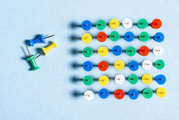 Multi-colored stationery buttons on a blue background stacked needles up