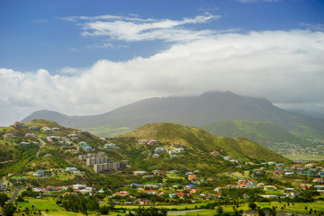A view over St. Kitts Island with residential area and lush green hills on the background