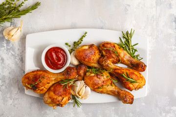Grilled spicy chicken legs baked with garlic, rosemary and thyme on white background.