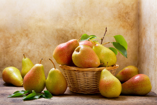 fresh pears with leaves in a basket