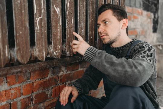 Alone autistic man sitting at the rusty radiator