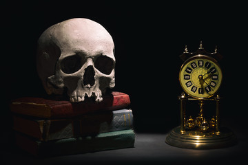 Human skull on old books near retro vintage clock on black background under beam of light. Dramatic concept.