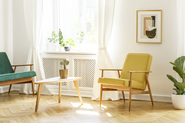 Poster above yellow wooden armchair at table in retro living room interior with window. Real photo
