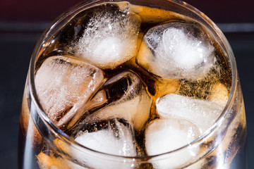Cola with ice cubes in a close-up glass