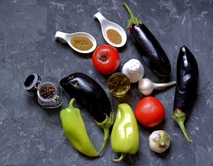 ngredients for preparation of salad  from eggplants, tomatoes and sweet peppers on a dark gray concrete background. Eggplants, tomatoes, sweet peppers, garlic, spices, salt, olive oil.