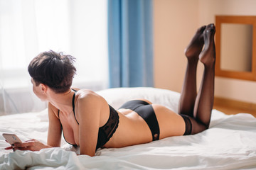 Indoor shot of sexy woman lying in black lingerie on bed with phone, showing her heels, while looking at the window. Waiting for call