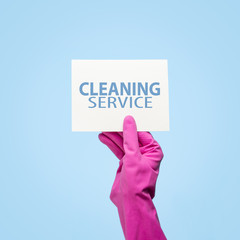 Female hand in pink gloves holds a card with text Cleaning services on a blue background. cleaning service concept. Flat lay, Top view