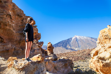 Young woman standing on the edge of rock looking to volcano