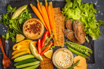 Vegetarian Arabic dip hummus with vegetables and different snacks on dark background. Healthy vegan food concept.