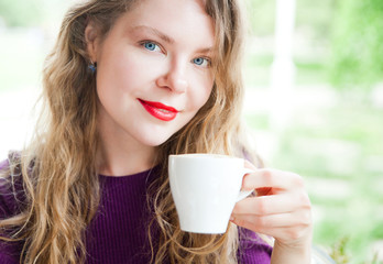 portrait of Beautiful woman with red lips holing white cup of coffee