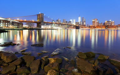 Wall Mural - Panorama of Brooklyn Bridge, East River and Manhattan at sunset with lights and reflections. New York