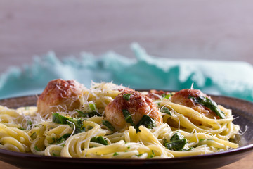 Pasta with meatballs and spinach. Spaghetti with meatballs in bowl on wooden table. horizontal