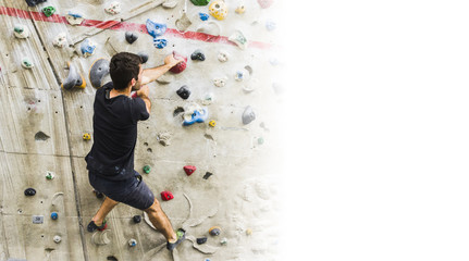 Man practicing rock climbing on artificial wall indoors. Active lifestyle and bouldering concept with copy space.