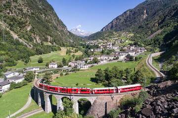 Bernina Express, red train of Bernina over the viaduct of Brusio, Unesco heritage