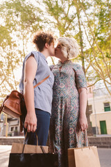 Young lesbian couple kissing each other on a city street