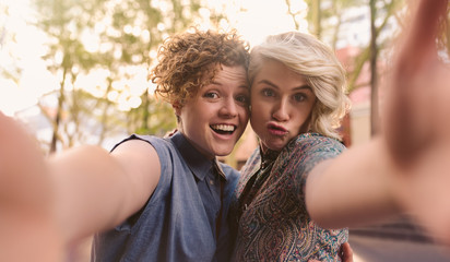 Smiling lesbian couple making faces and taking selfies together outside