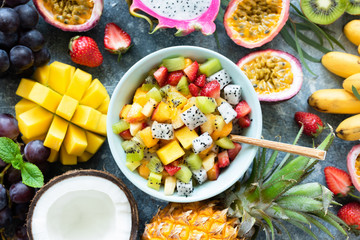 Tropical fruit salad with mango and pitaya in bowl. Healthy salad. Mango, coconut, pineapple, pitaya, mango and passion fruit salad