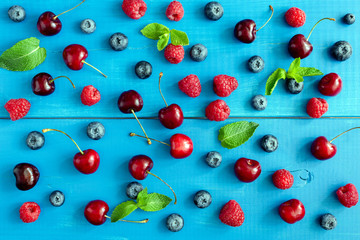 Berries on blue background, flat lay. Berry pattern on blue wood background. Raspberry, sweet cherry, blueberry and mint leaf pattern